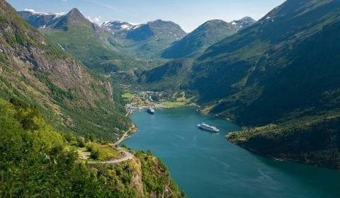 Altas montañas verdes que rodean el fiordo de Geiranger donde hay dos barcos en el puerto, vista desde la carretera del Águila