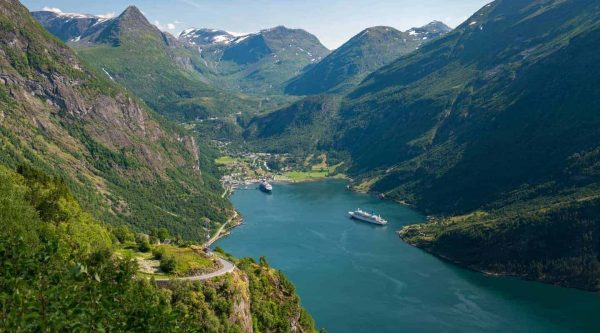 High green mountains surrounding the Geirangerfjord where two ships are in port, view from the Eagle Road