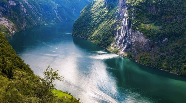 The waterfall of the Seven Sisters streaming down a steep mountain in the turqoise Geirangerfjord