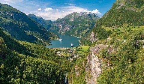 Vue imprenable de Flydalsjuvet, montagnes verdoyantes entourant le Geirangerfjord sous un ciel bleu, deux navires visitant Geiranger, Norvège