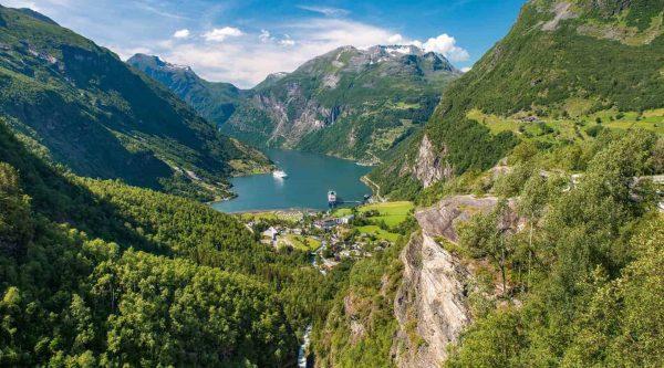 Prachtig uitzicht vanaf Flydalsjuvet, de Geirangerfjord omringd door groene bergen onder een blauwe hemel, twee cruiseboten op bezoek in Geiranger, Noorwegen