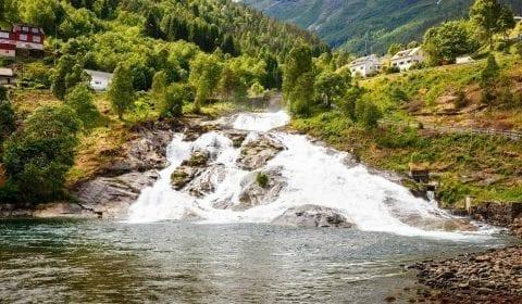 Cascade descendant les montagnes verdoyantes, maisons en bois à Hellesylt, Norvège