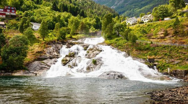 Waterfall streaming down the green mountains, wooden houses in Hellesylt, Norway