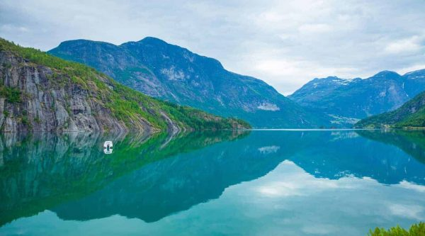 Turquoise coloured lake of Oppstrynsvatnet between Hellesylt and Geiranger, surrounded by mountains, Norway