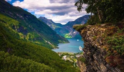 Vista panoramica dalla gola di Flydalsjuvet verso il fiordo di Geiranger, patrimonio UNESCO, poche nuvole sopra le montagne verdi