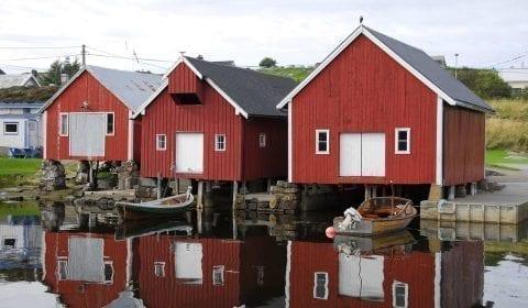 Casetas rojas y blancas de madera para barcos en la orilla del mar en el pueblo de Bud, cerca de Molde, Noruega