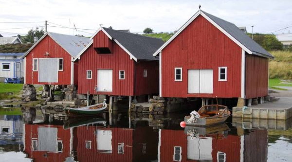 Red and white wooden boathouses on the waterside in the village of Bud, close to Molde, Norway