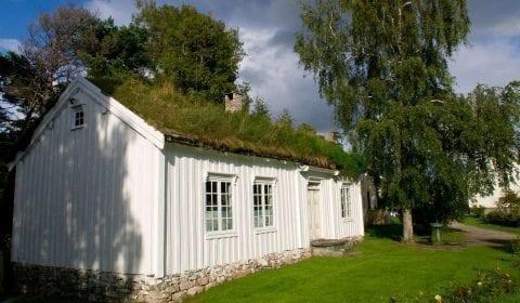 Casa de madera blanca con tejado de hierba y jardín verde en Molde, Noruega