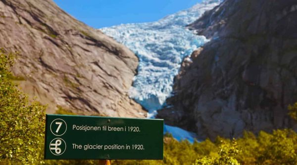 Sign stating end of the glacier in 1920 with current Briksdal glacier surrounded by mountains in the background, Olden, Norway