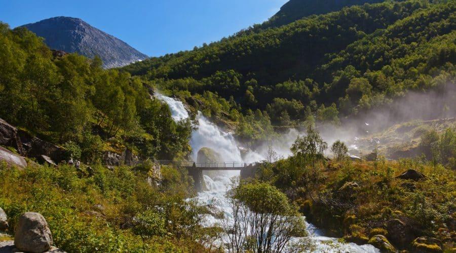 De spectaculaire Kleivafossen waterval loopt langs een berg naast het wandelpad wat naar de Briksdal Gletsjer leidt, Olden, Noorwegen