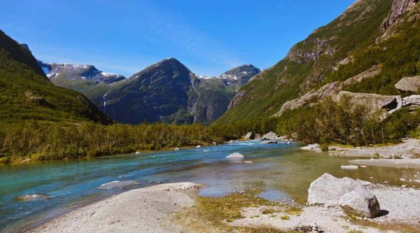 Clear blue water from the Briksdal glacier streaming between the green mountains, Olden, Norway