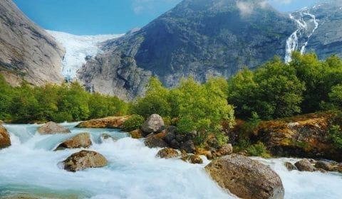 The Briksdal glacier, arm of the Jostedal Glacier, hanging from a mountain, fresh water passing in a stream, Olden, Norway