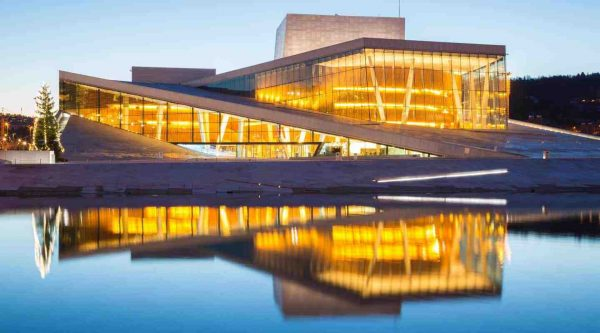 The Oslo Opera House with lights on, reflecting in the water