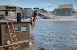Three women jump from a floating sauna into the Oslo Fjord across from the Opera House