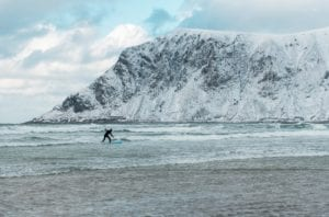 A surfer surfs in the waters of Lofoten, Norway