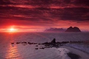 A pink glow from the midnight sun over the ocean in Norway.