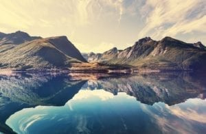 A view of a mountain range in the background with a beautiful lake reflecting the mountains in the foreground, Norway.