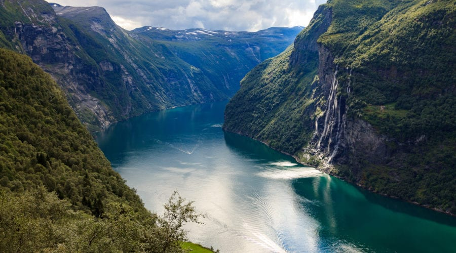 a view looking over the Geirangerfjord and the Seven Sisters waterfall across the fjord