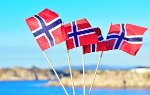 Norwegian flags flying in front of a beautiful Norwegian landscape.