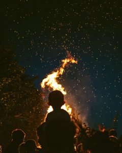 A silhouette of a child on their parent's shoulders watching a midsummer bonfire