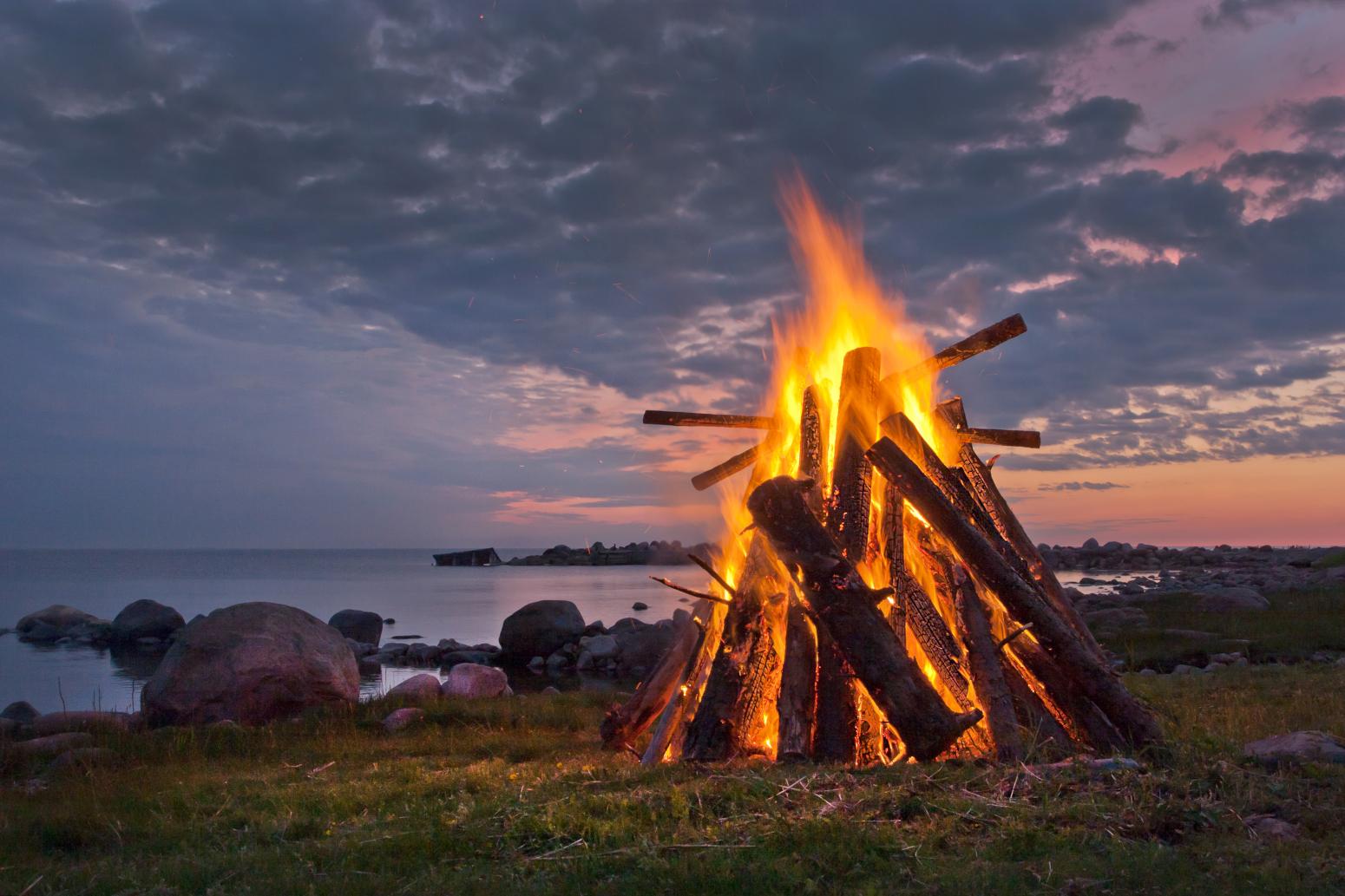a bonfire next to the ocean during midsummer