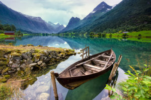 a wooden boat is docked on the side of the beautiful Loen lake in Norway.