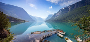 A view of row boats docked on the side of Lovatnet, a beautiful turquoise-blue lake in Norway.