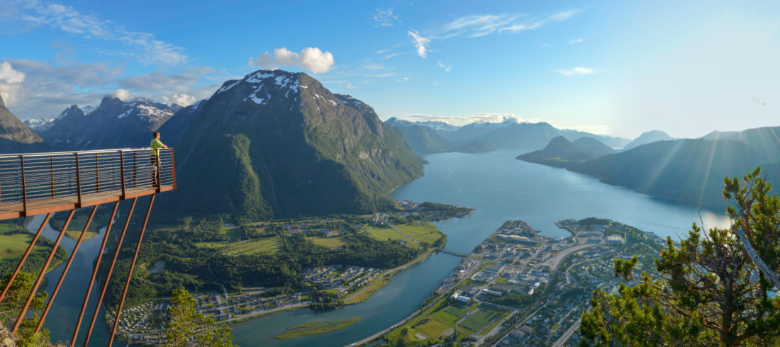 A view of Rampestreken viewing platform and the Romsdal valley, mountains, and fjord below.