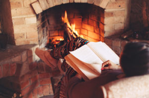 A woman reading a book by a fireplace inside of a cabin